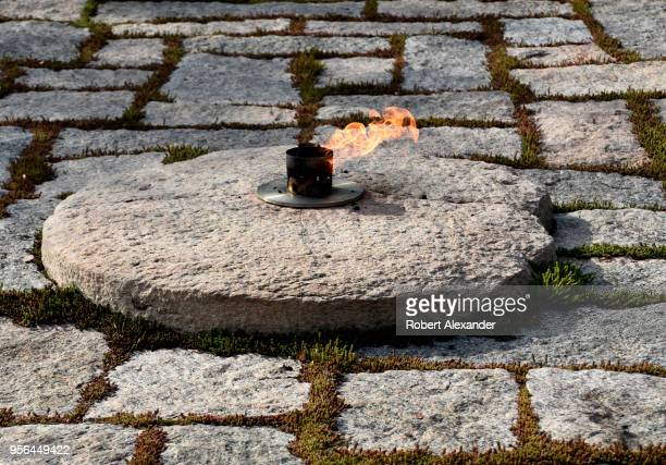 The John F Kennedy Eternal Flame burns at the gravesite of former US President John F Kennedy and his wife Jacqueline Kennedy Onassis at Arlington...
