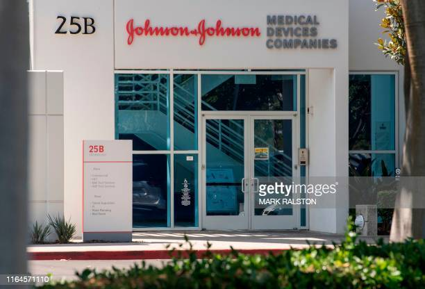 The Johnson & Johnson logo is seen above an entrance to a building at their campus in Irvine, California on August 28, 2019. - The US pharmaceutical...