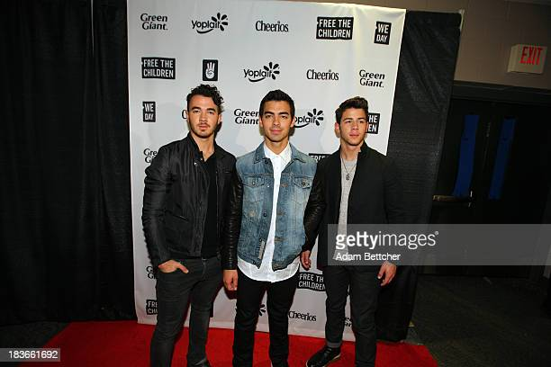 The Jonas brothers pose during the red carpet before the We Day Minnesota event at the Xcel Energy Center in St Paul Minnesota on October 8 2013