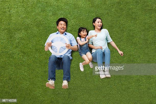The joy of a family of three in lying on the grassland