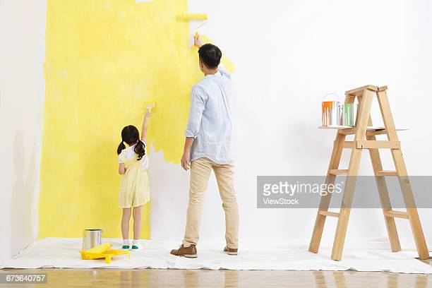 The joy of the father and daughter in the paint for the walls