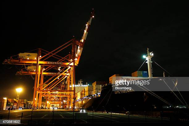 The JPO Tucana container ship prepares to moor at the dock next to gantry cranes at a shipping terminal at night in Tokyo Japan on Tuesday April 21...