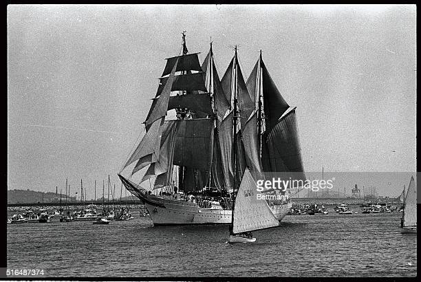 The Juan Sebastian De Elcano of Cadiz Spain a fourmasted topsail schooner looks even more impressive when contrasted with the small sailing craft...