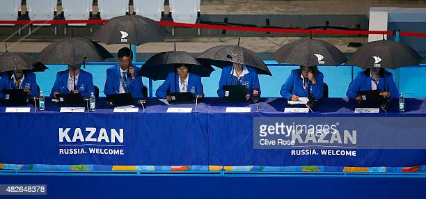 The judges shelter from the rain in the Women's Free Combination Synchronised Swimming Final on day eight of the 16th FINA World Championships at the...