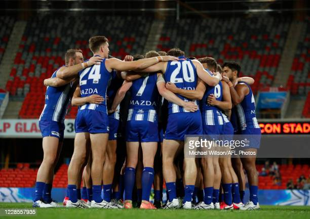 The Kangaroos huddle during the 2020 AFL Round 18 match between the North Melbourne Kangaroos and the West Coast Eagles at Metricon Stadium on...