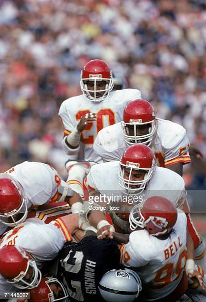 The Kansas City Chiefs defense takes down Los Angeles Raiders running back Frank Hawkins during a game at Los Angeles Memorial Coliseum on October 6...