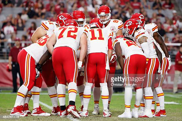 The Kansas City Chiefs huddle up around quarterback Alex Smith during the preseason NFL game against the Arizona Cardinals at the University of...