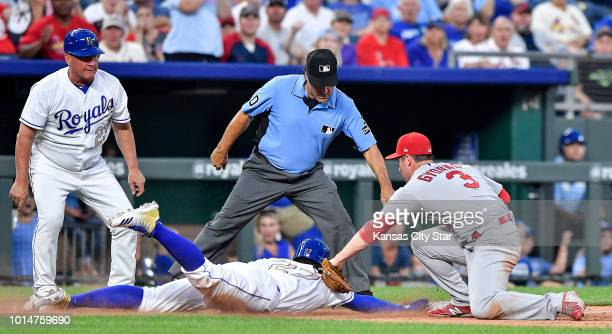 The Kansas City Royals' Adalberto Mondesi dives safely back to third before the tag from St Louis Cardinals third baseman Jedd Gyorko on a fly ball...