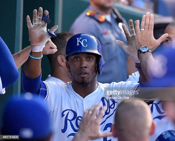 The Kansas City Royals' Alcides Escobar is congratulated after scoring on his own RBI triple after a throwing error by Detroit Tigers shortstop Jose...