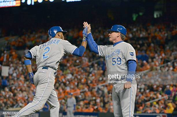 The Kansas City Royals' Alcides Escobar is congratulated by third base coach Mike Jirschele after a home run in the third inning against the...