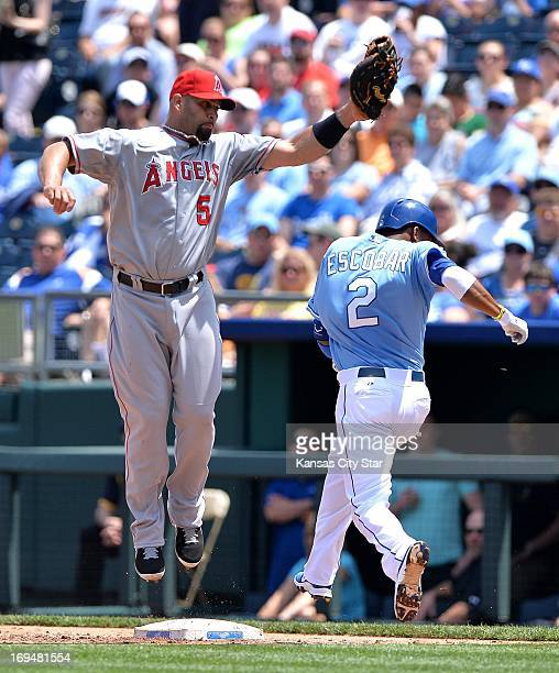 The Kansas City Royals' Alcides Escobar reaches first before the tag off a high throw to Los Angeles Angels first baseman Albert Pujols in the fourth...