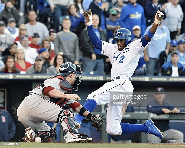The Kansas City Royals' Alcides Escobar scores as Boston Red Sox catcher Christian Vazquez drops the ball on a double by Norichika Aoki in the first...