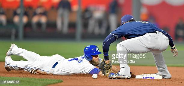 The Kansas City Royals' Alex Gordon dives back to second as the throw to Milwaukee Brewers second baseman Jonathan Villar bounces off his glove on a...