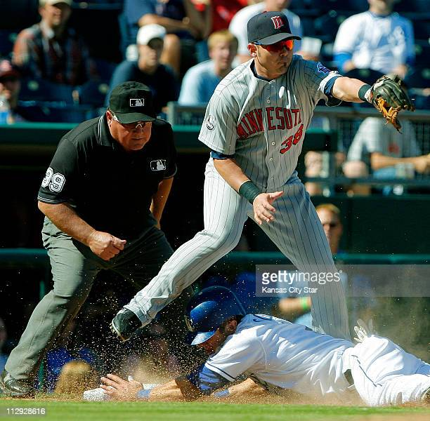 The Kansas City Royals' Alex Gordon slides safely into third in front of the Minnesota Twins' Luis Rodriguez on a sacrifice fly in the seventh inning...
