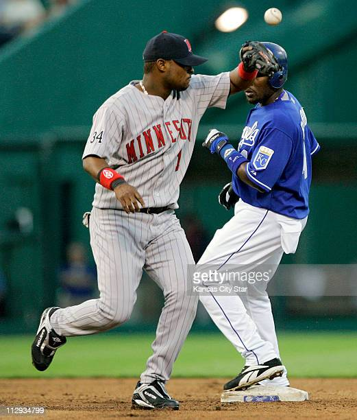 The Kansas City Royals Angel Berroa finishes up a double as the throw to Minnesota Twins' Luis Castillo bounces off his glove in the fourth inning at...