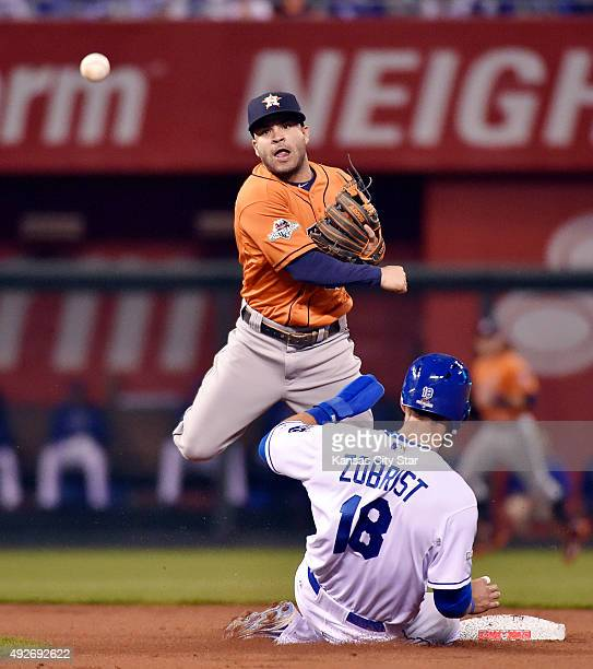 The Kansas City Royals' Ben Zobrist slides into second under Houston Astros second baseman Jose Altuve who completes a double play in the first...