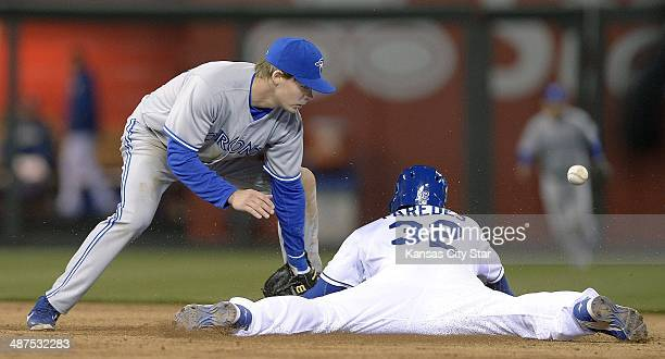 The Kansas City Royals' Jimmy Paredes steals second base as the throw skips past Toronto Blue Jays second baseman Chris Getz in the seventh inning at...