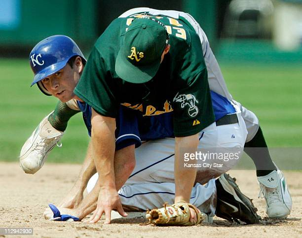 The Kansas City Royals Mark Teahen ends up under Oakland Athletics shortstop Bobby Crosby after Crosby completed a double play in the sixth inning...