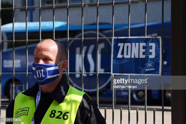 The Karlsruhe team bus is seen in the backgrund as a steward stands in front of a security gate marking zone 3 prior to the Second Bundesliga match...
