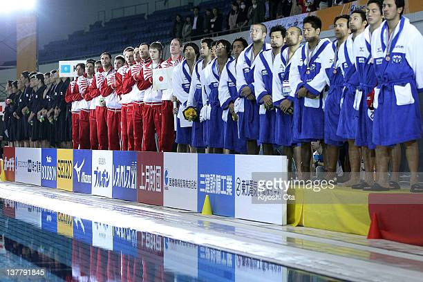 The Kazakhstan team sing their national anthem next to the China team and Japan team on the podium during the award ceremony after victory in the...