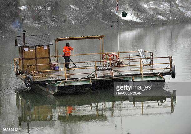 The keeper of the smallest Croatian public river ferry line crosses the frozen Kupa river on his ferry-boat, some 60 kilometers south of capital...