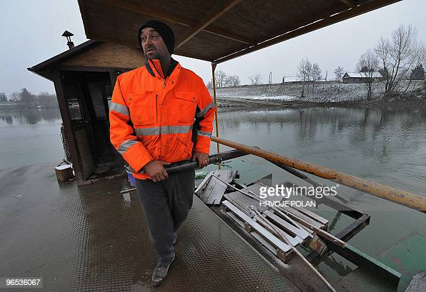 The keeper of the smallest Croatian public river ferry line manoeuvres his ferry-boat on the frozen Kupa river, some 60 kilometers south of capital...