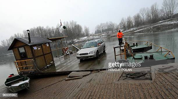 The keeper of the smallest Croatian public river ferry line manoeuvres his ferry-boat to the frozen Kupa river, some 60 kilometers south of capital...