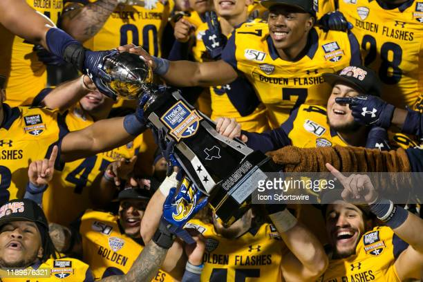 The Kent State Golden Flashes celebrate winning the Tropical Smoothie Cafe Frisco Bowl trophy after the game between the Utah State Aggies and the...