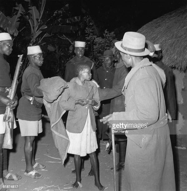 The Kenyan police help to arrest a young female member of the Mau Mau rebellion during a night raid 29th November 1952 Original Publication Picture...