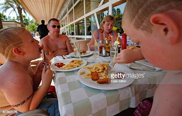 The Kerr family from Northern Ireland enjoy their lunch while on holiday at the Costa Encantada hotel on August 15 2008 in Lloret de Mar Spain Having...