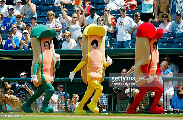 The ketchup hot dog has trouble keeping his pants up as he leads the hot dog race between innings during the game between the Kansas City Royals and...