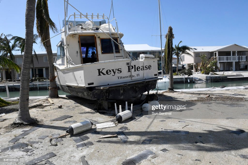 The Keys Please boat sits on the seawall along a canal in a community on Cudjoe Key, Fla., on Tuesday, Sept. 12, 2017. The boat originally was moored to the dock inside the canal, but the force of Hurricane Irma pushed the boat on land.