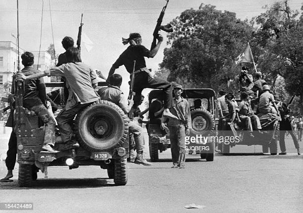 The Khmer Rouge guerilla soldiers wearing black uniforms drive 17 April 1975 atop jeeps through a street of Phnom Penh the day Cambodia fell under...