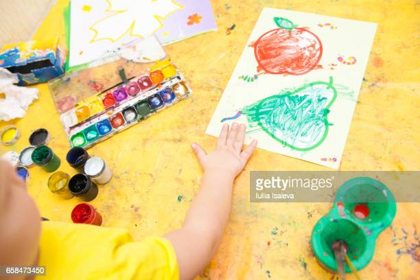 The kid painting the fruits