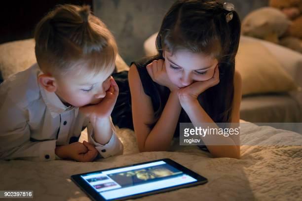 Les enfants regardent un film sur la tablette. Jeux et divertissement.
