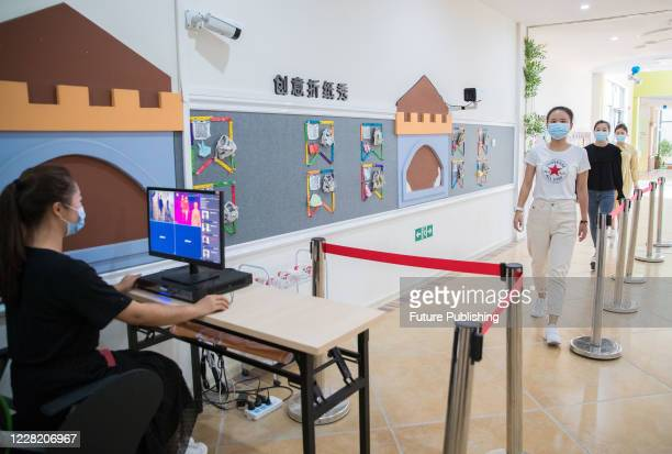 The kindergarten teacher simulated the temperature of the children entering the school. Hohhot City, Inner Mongolia, China, August 26,...