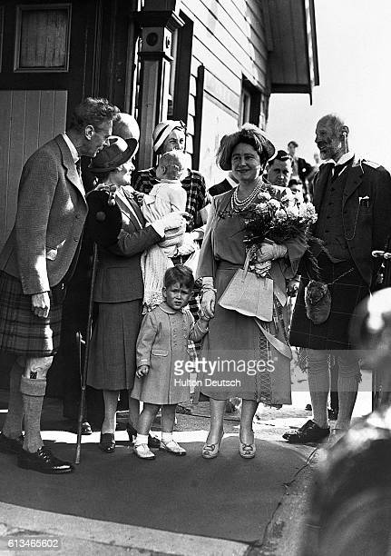 The King and Queen with their grandchildren Prince Charles and Princess Anne at Ballater Station, in Scotland, on their way to start their holiday at...