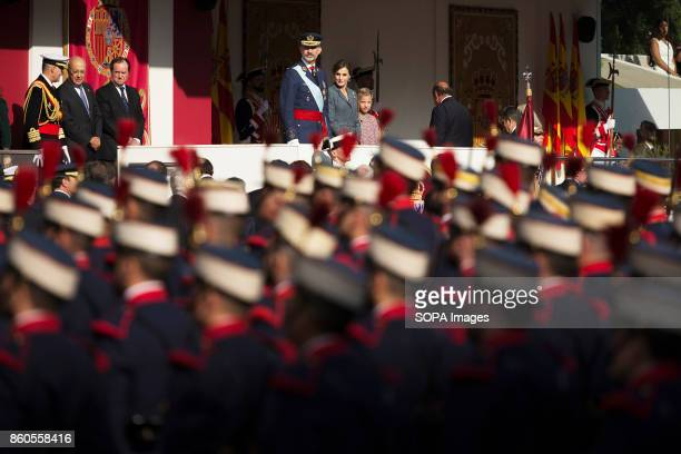 The King of Spain Felipe VI and the Queen Letizia of Spain are pictured while watching the parade through the streets of Madrid National day military...