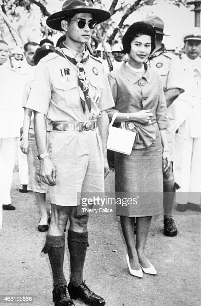 The king of Thailand Bhumibol Adulyadej accompanied by queen Sirikit stands as a boy scout The king is the chief of the National Scout Organization...