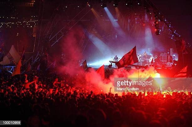 The Kings of Leon on the Pryramid Stage in front of crowds bathed in red smoke at Glastonbury 27th June 2008