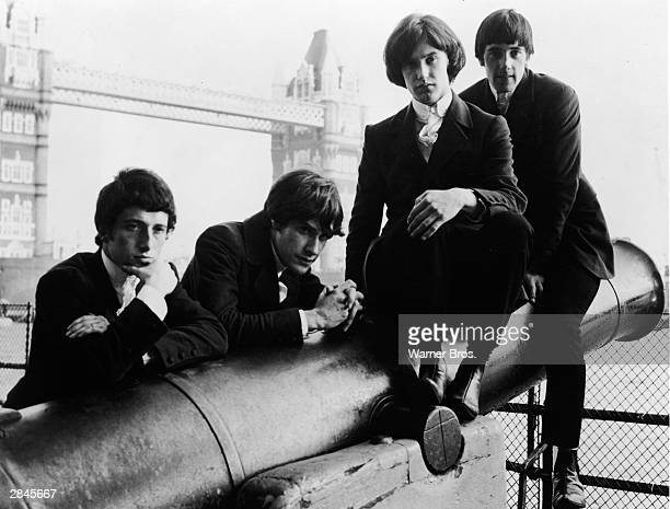 The Kinks Peter Quaife Ray Davies Dave Davies and Mick Avory pose on a cannon in a promotional picture with Tower Bridge in the background London...