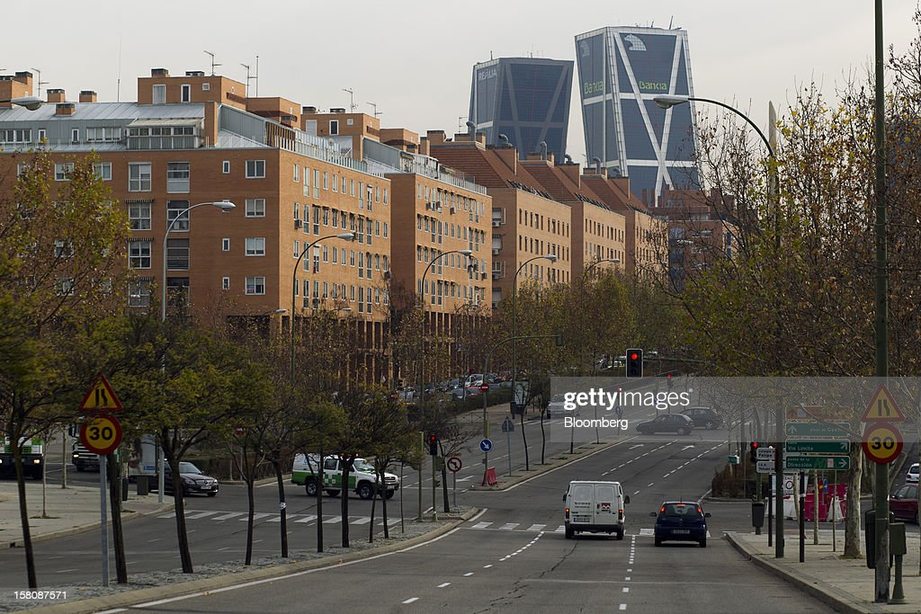 The Kio towers, headquarters of Bankia SA, stand behind residential apartment blocks in a suburb of Madrid, Spain, on Monday, Dec. 10, 2012. The jobless rate in Spain stands at 26 percent, jostling with Greece for the rank of highest on the continent. Photographer: Photographer: Angel Navarrete/Bloomberg via Getty Images