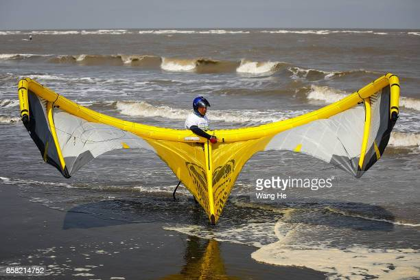 The Kite surfers prepares his kite at Qidong Golden Beach before the start of the 3rd Qidong YuanTuoJiao Kite Surfing Invitational Tournament on...