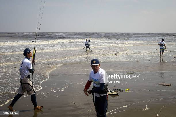The Kite surfers prepares their kite at Qidong Golden Beach before the start of the 3rd Qidong YuanTuoJiao Kite Surfing Invitational Tournament on...