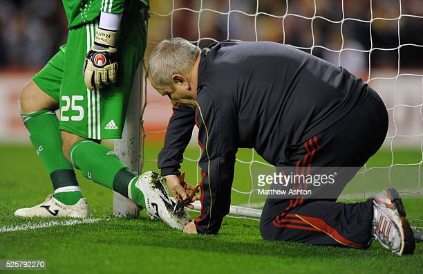 The kitman adjusts the studs on the boots of Pepe Reina of Liverpool