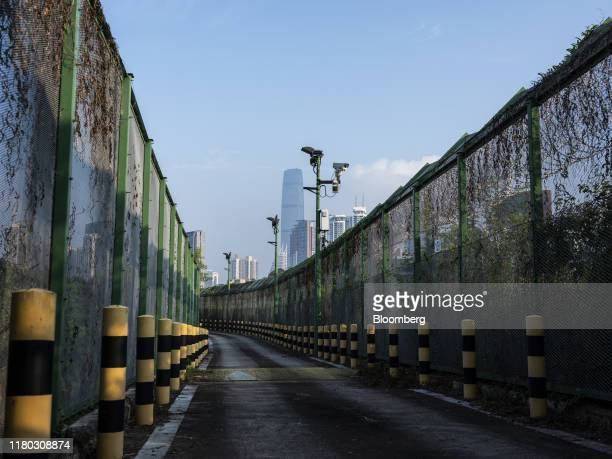 The KK100 building, center, and other buildings in Shenzhen stand beyond the fenced off Border Road in the Lo Wu district of Hong Kong, China, on...