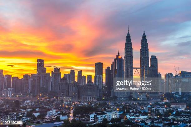 kuala lumpur, malaysia - dec 6, 2015: the klcc twin towers with orange sunrise background with natur - natur stock pictures, royalty-free photos & images