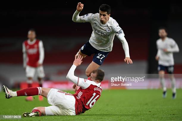 The knee of Joao Cancelo of Manchester City connects with the head of Rob Holding of Arsenal during the Premier League match between Arsenal and...