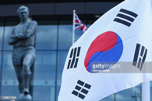 The Korea Republic flag is unfurled in front of the Bobby Moore statue ahead of the Men's Football first round Group B Match between Korea Republic...