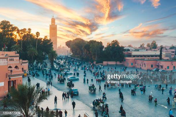 the koutoubia mosque's minaret and tourists in djemaa el fna square at sunset, marrakech, morocco - marrakech photos et images de collection